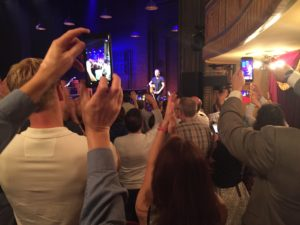 Springsteen stands on a Broadway stage looking at the faces in the crowd.